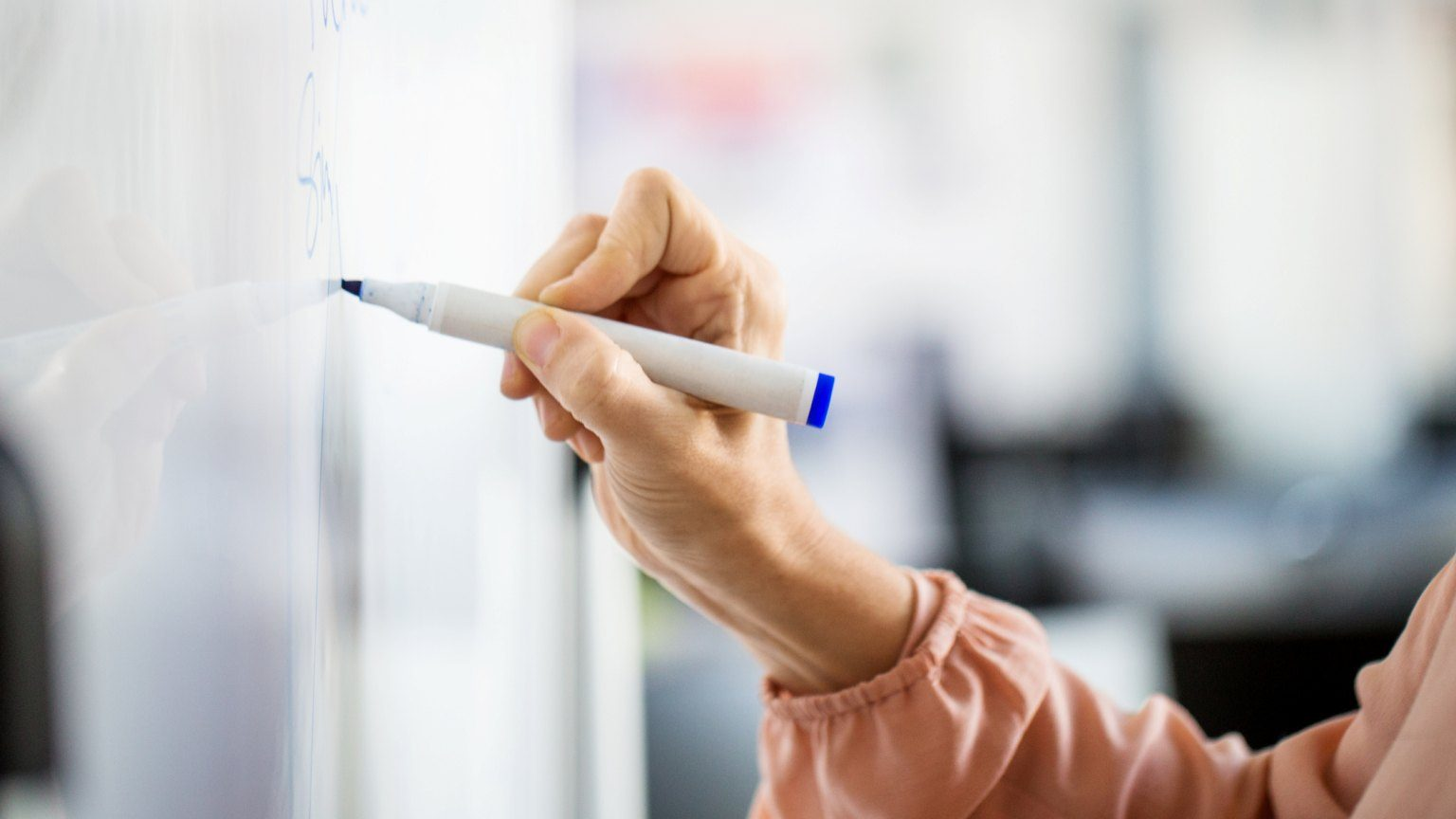 Cropped hand of businesswoman writing on whiteboard during meeting at creative office