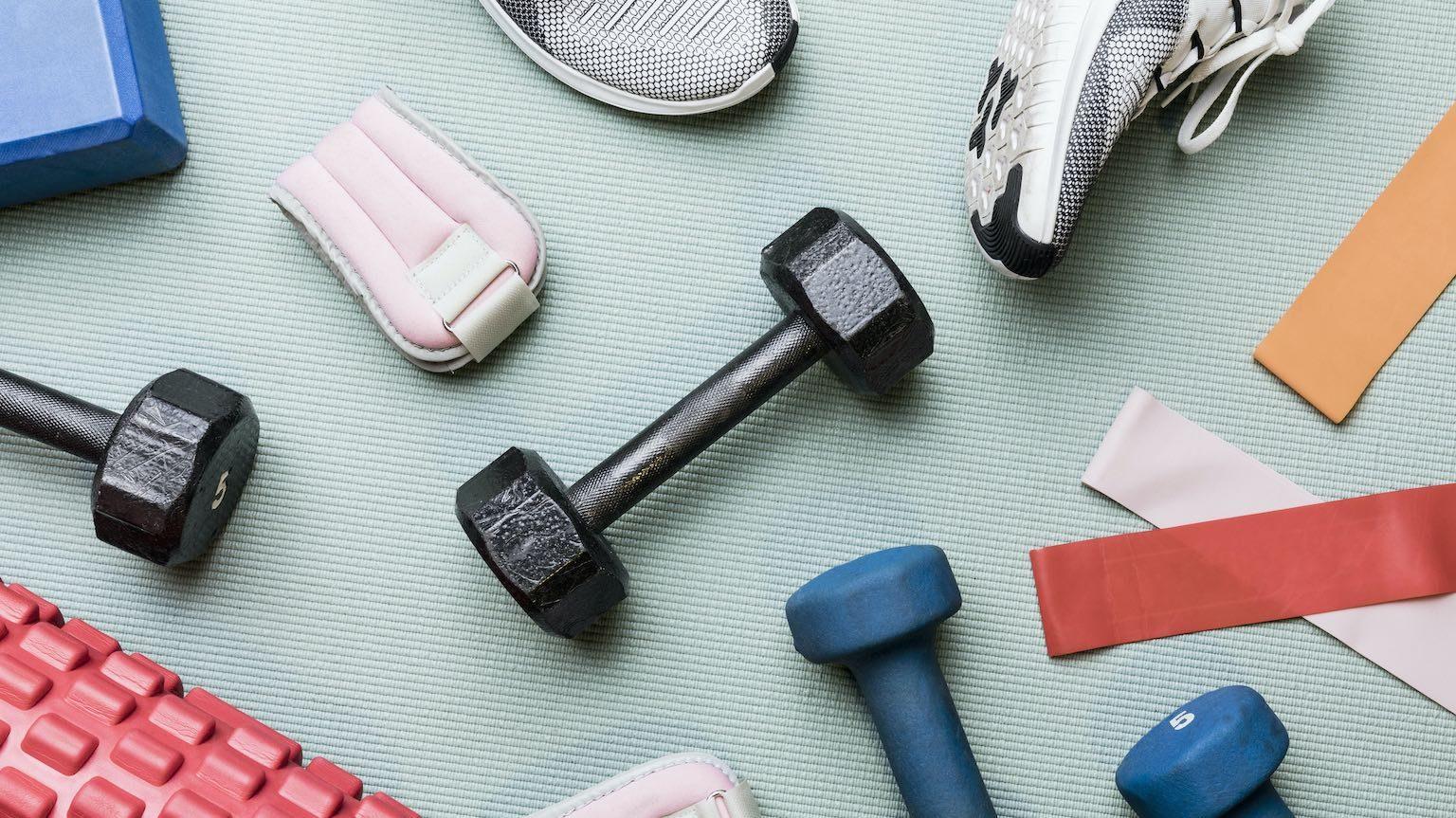 Dumbbells, resistance bands, foam roller on exercise mat.