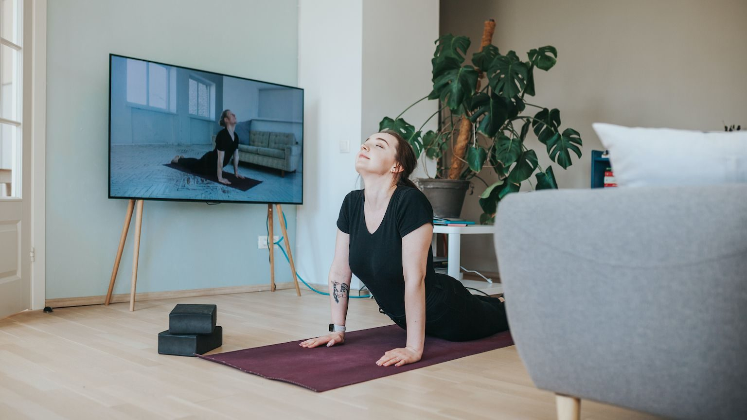 Woman doing yoga at home while watching a yoga video on her TV