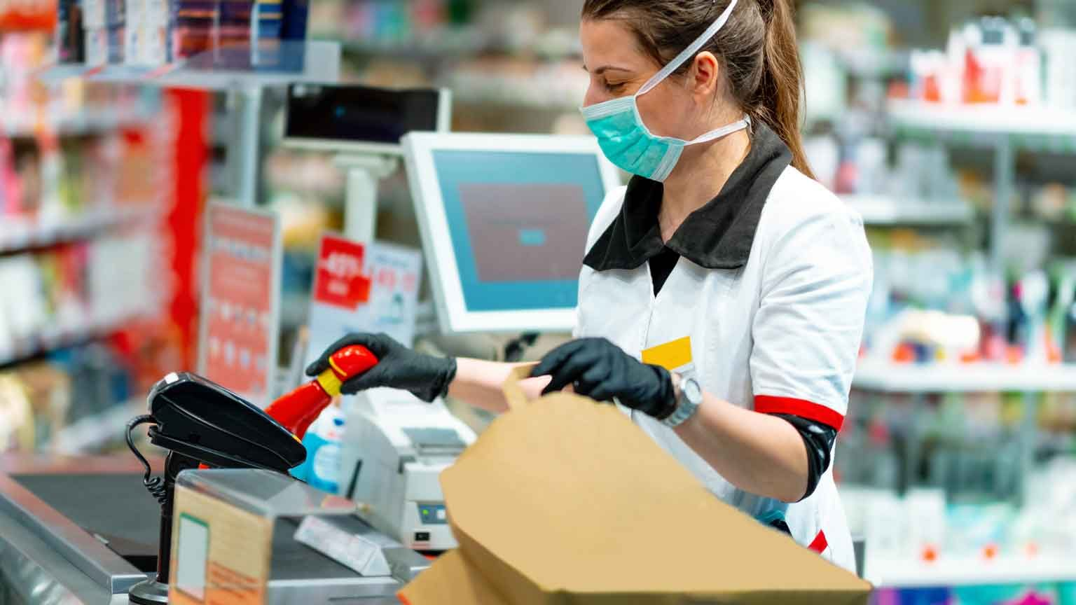 Woman cashier in mask and gloves working at the register