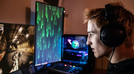 Profile View of Male Gamer Playing Competitive Online Games with great Concentration - stock photo