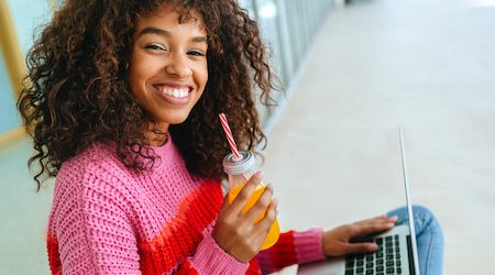 Portrait of smiling woman with laptop and juice
