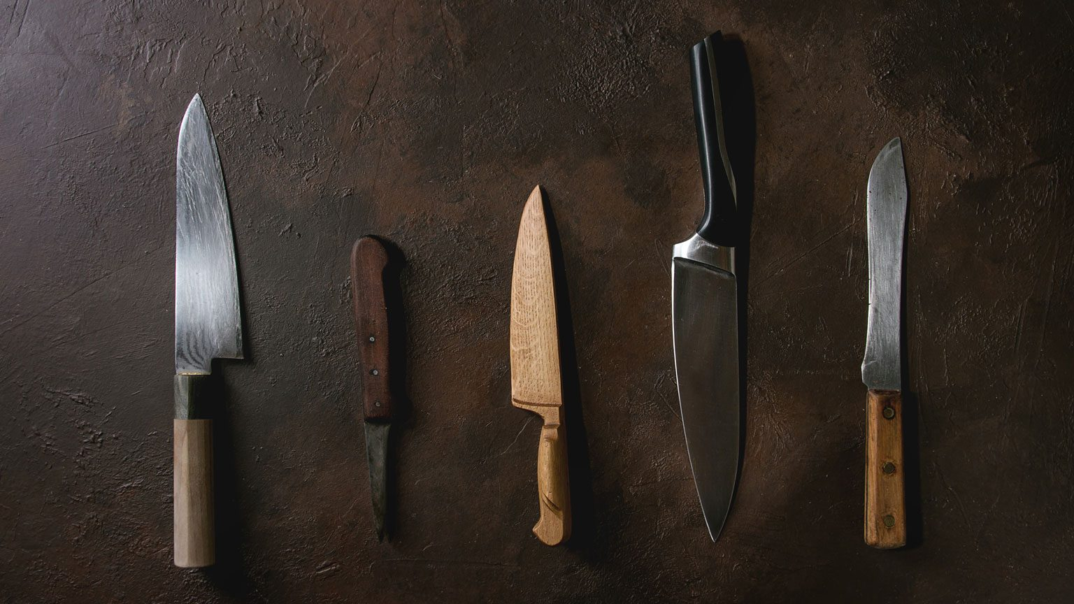 Collection of different kitchen metal, wooden and vintage knives in row over dark brown texture background.