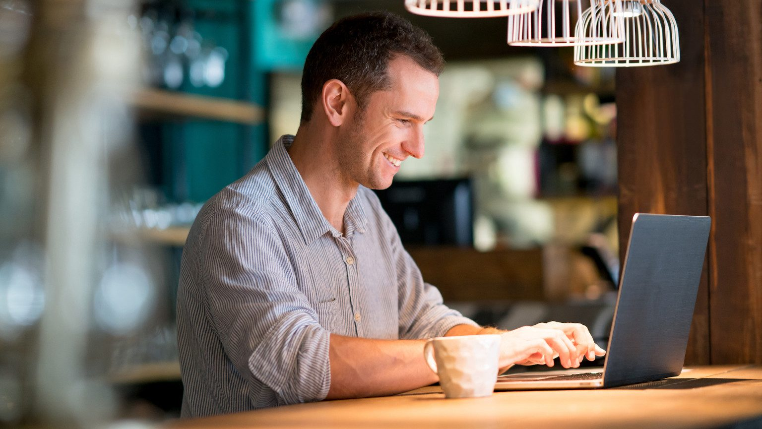 Portrait of a happy man working online at a cafe and drinking a cup of coffee