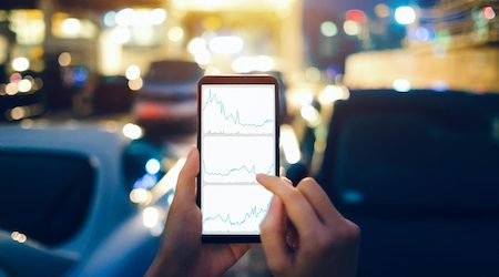Human hands checking financial trading data on mobile phone while walking to car in parking lot