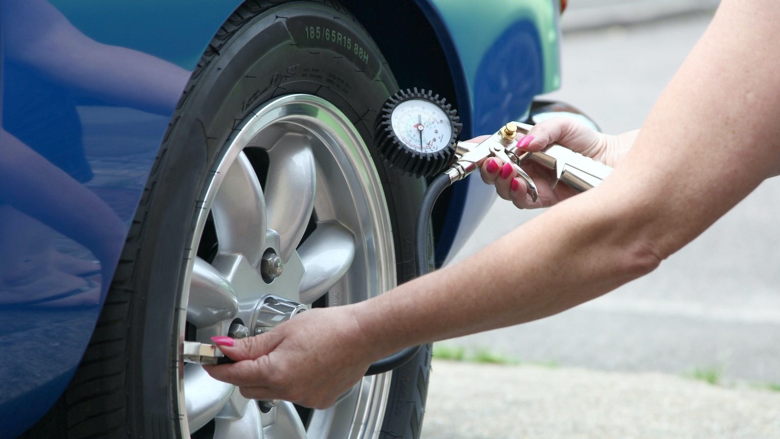 Female car maintenance using a  tyre pressure gauge to check the pressures on a classic  car tyre.