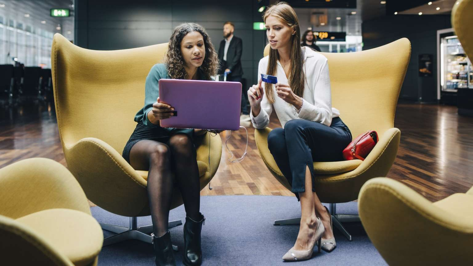 Women shopping on laptop in airport lounge