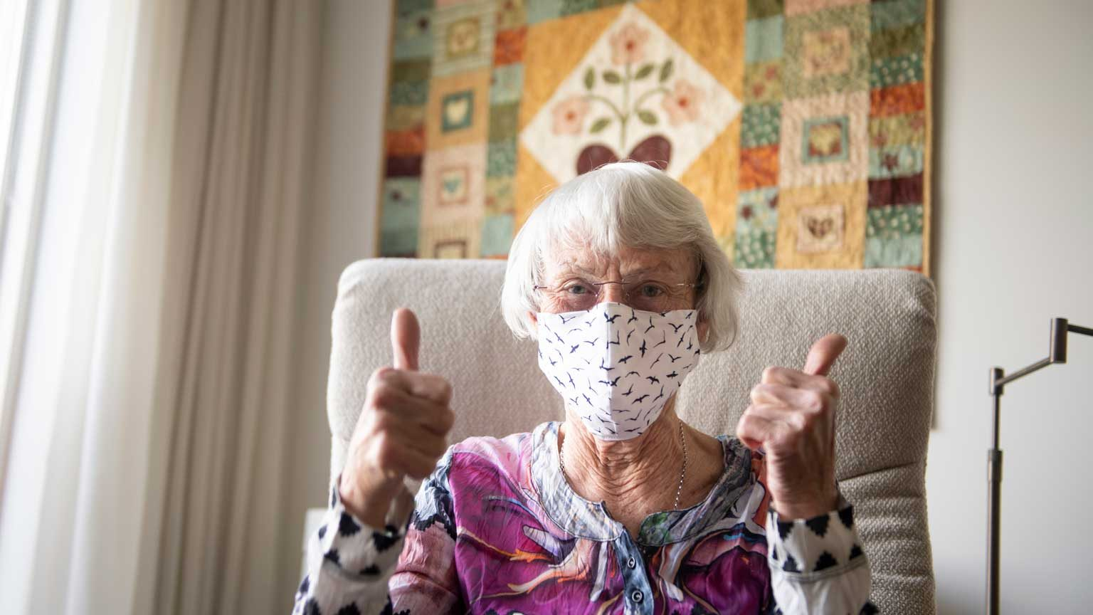 Senior woman with a home made face mask showing thumbs up