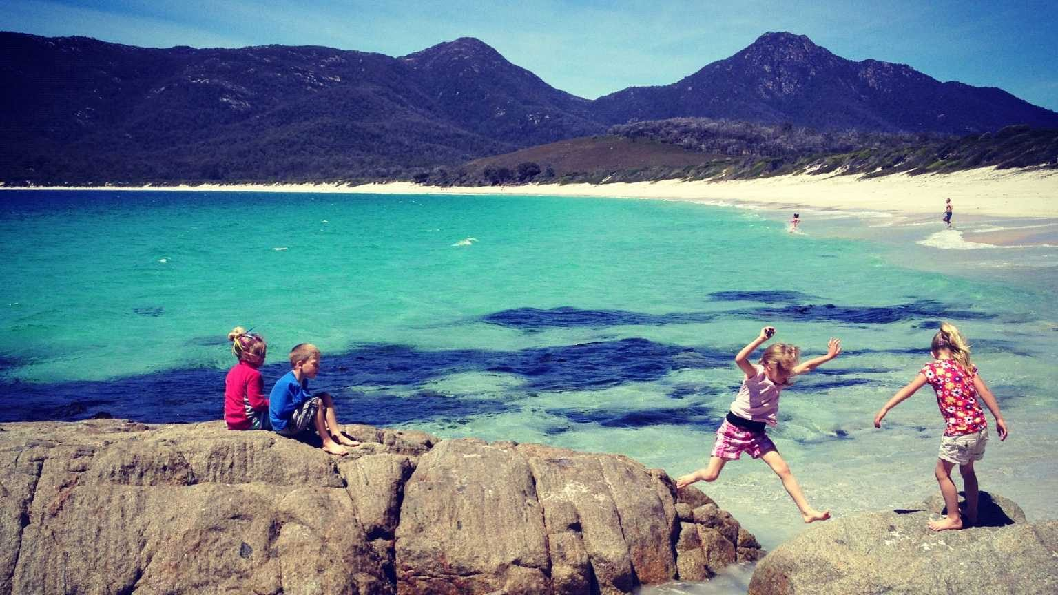 Children playing on rocks at the beach at Freycinet National Park.