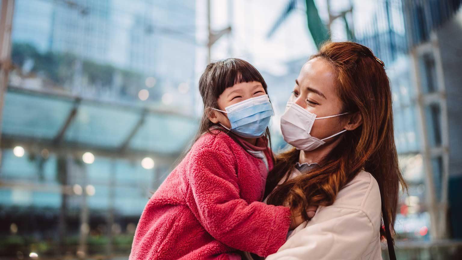 Mom & daughter in medical face masks talking joyfully in train station