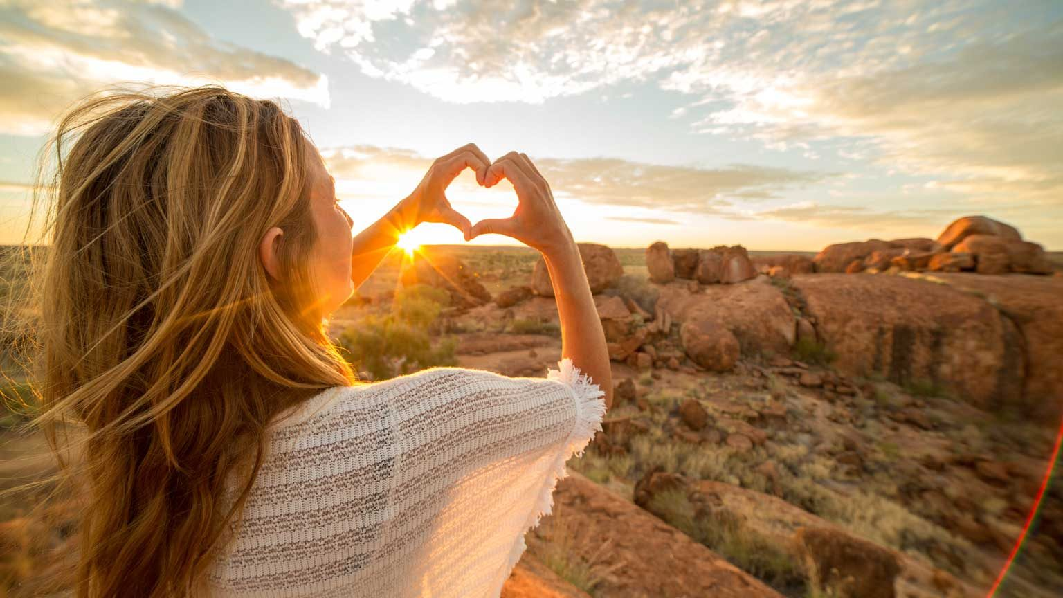 Young woman at the devil's Marbles makes a heart shape finger frame to the spectacular landscape at sunrise. Devils Marbles Conservation Reserve, Northern Territory, Australia.