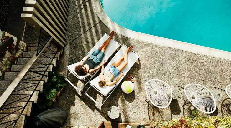 coupleholdinghandswhilerelaxinginloungechairs_Getty_738x4101