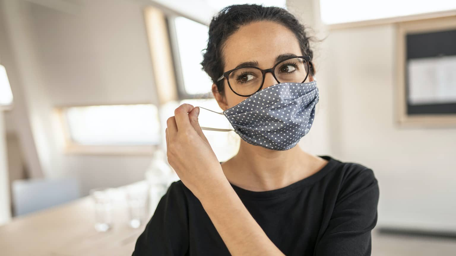 Woman with short hair and glasses wearing a cloth face mask