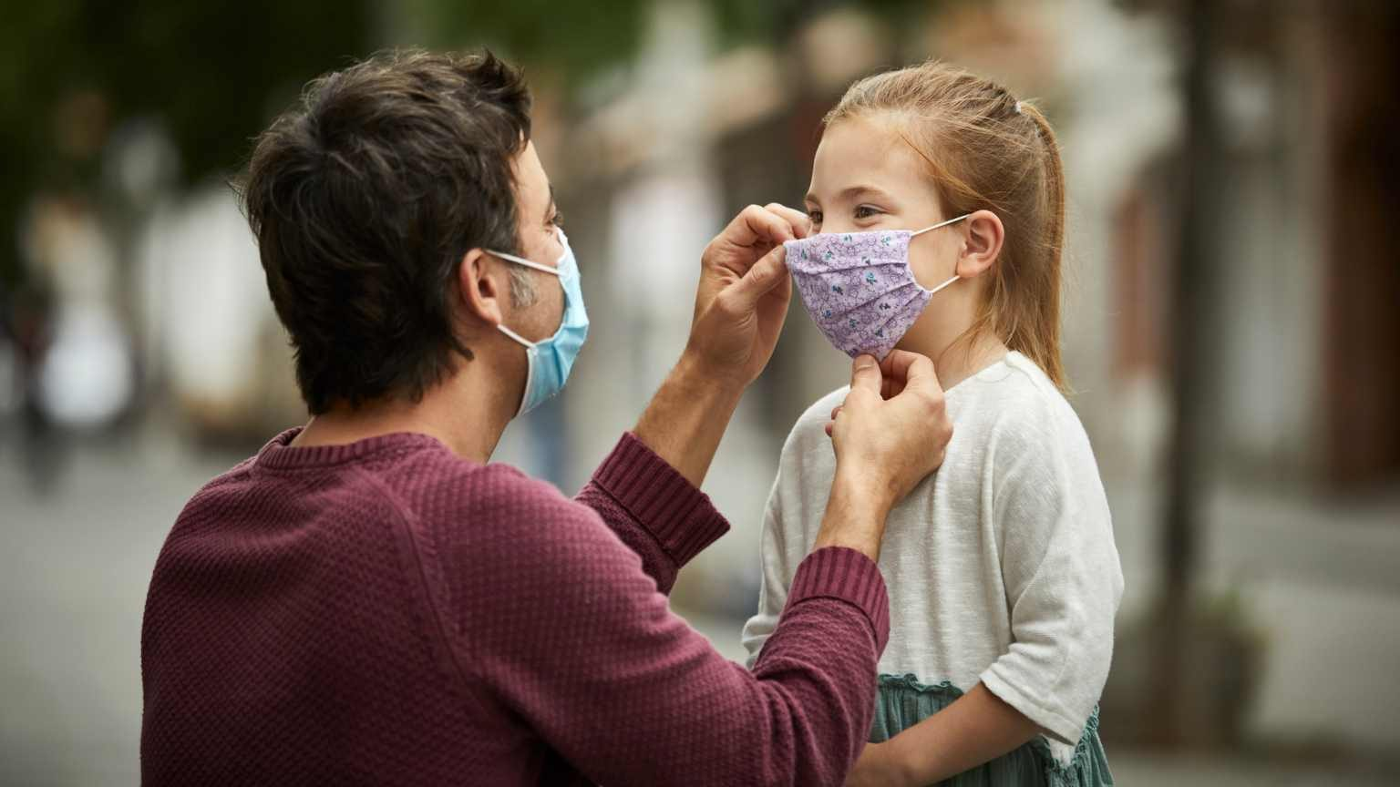 Father with surgical face mask, is putting a hand made protective face mask on his little daughter for the COVID-19 pandemic.
