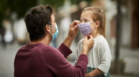 Father Putting Home Made Face Mask on Little Daughter