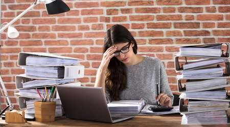 girl-with-piles-of-work-450