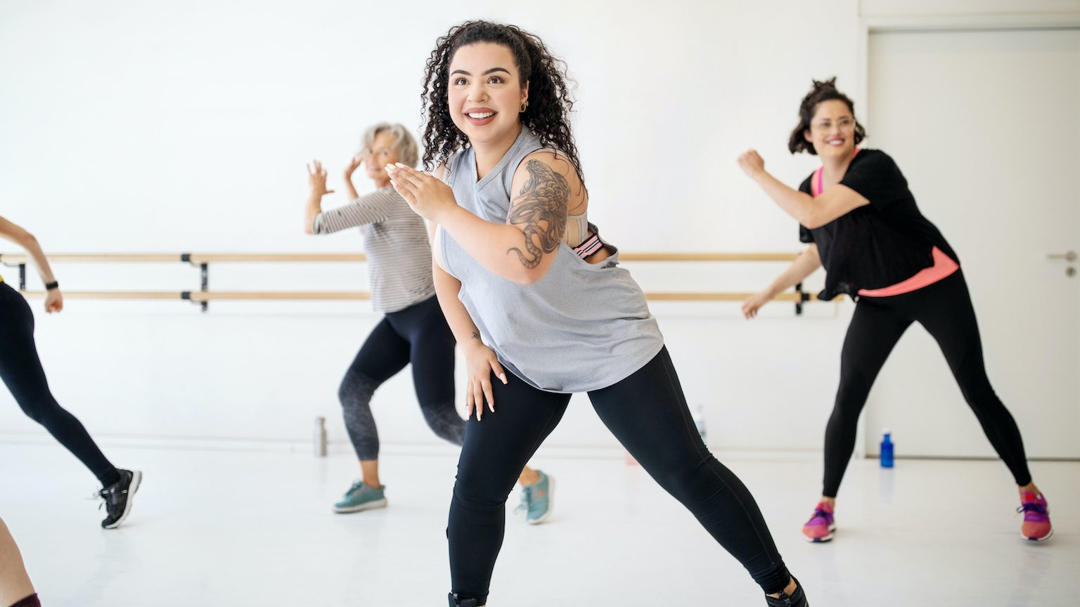 Woman learning fitness dance moves at health club. Female students learning dance in a fitness class.
