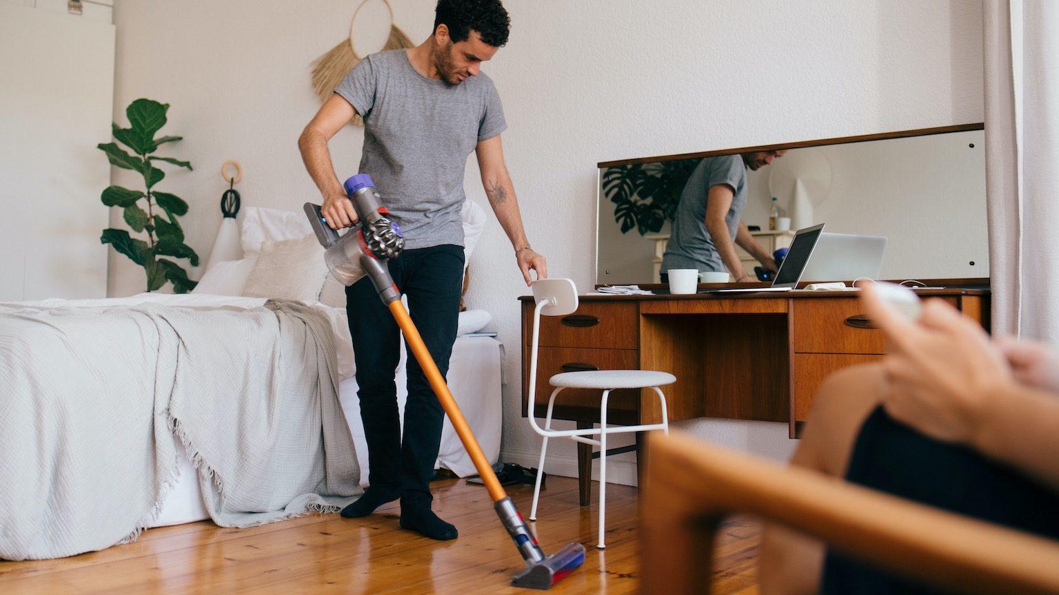 Man vacuuming a hardwood floor using a stick vacuum