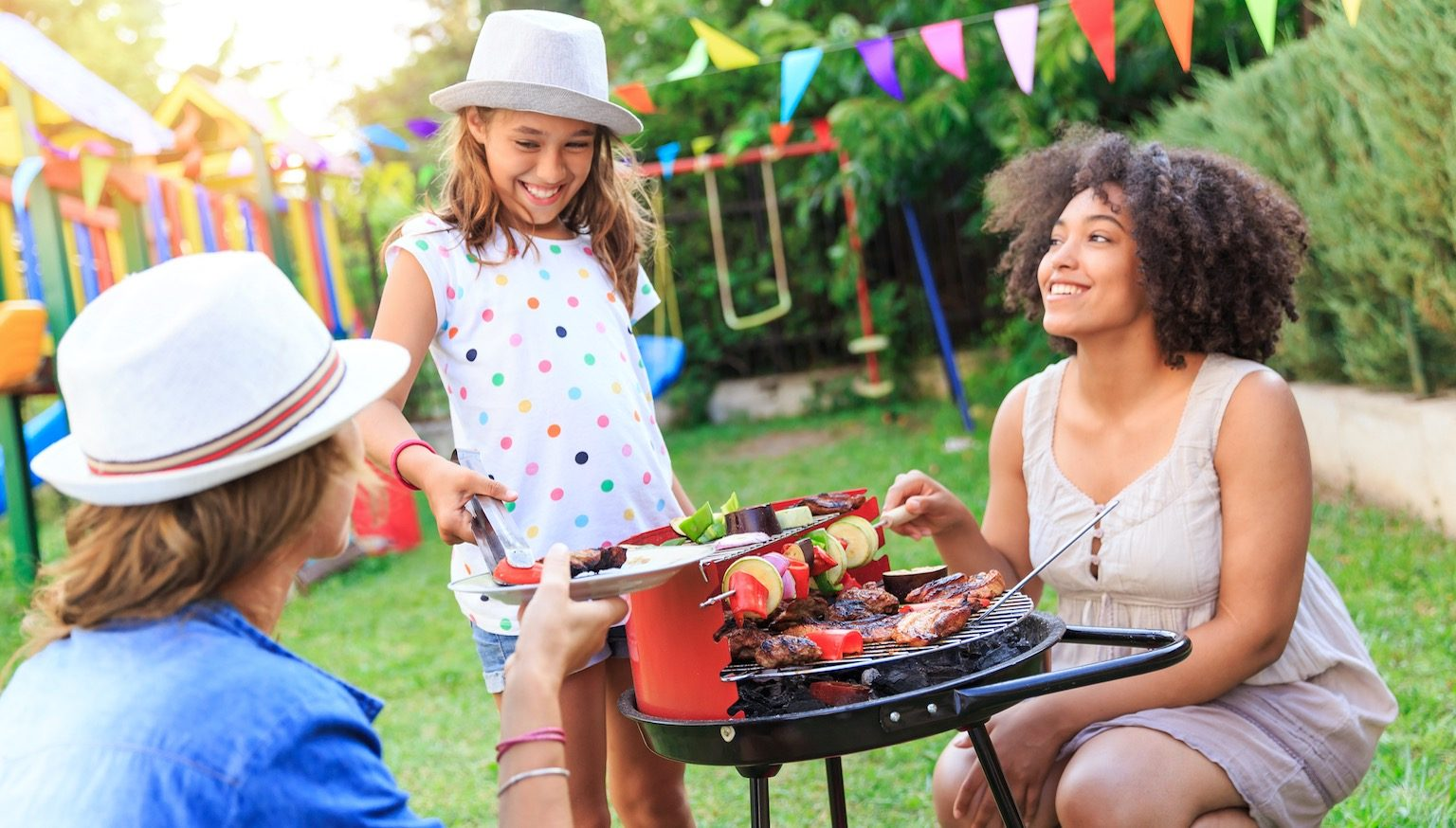 Family cooking on a barbecue in a backyard