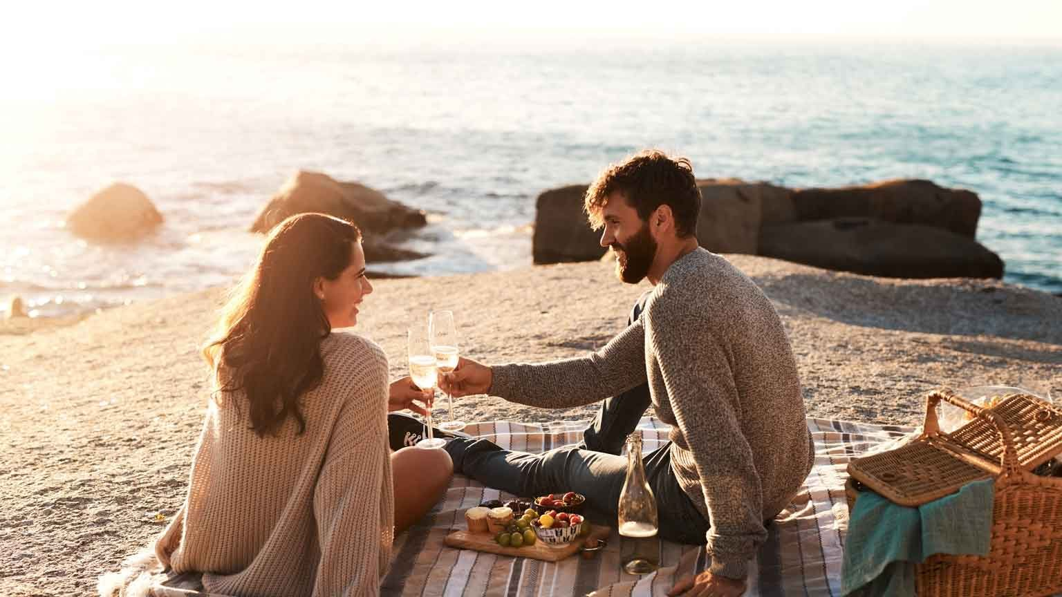 hot of a happy young couple having a picnic and toasting with wine at the beach
