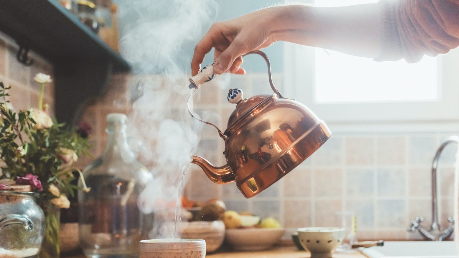 Man pouring hot water from the kettle