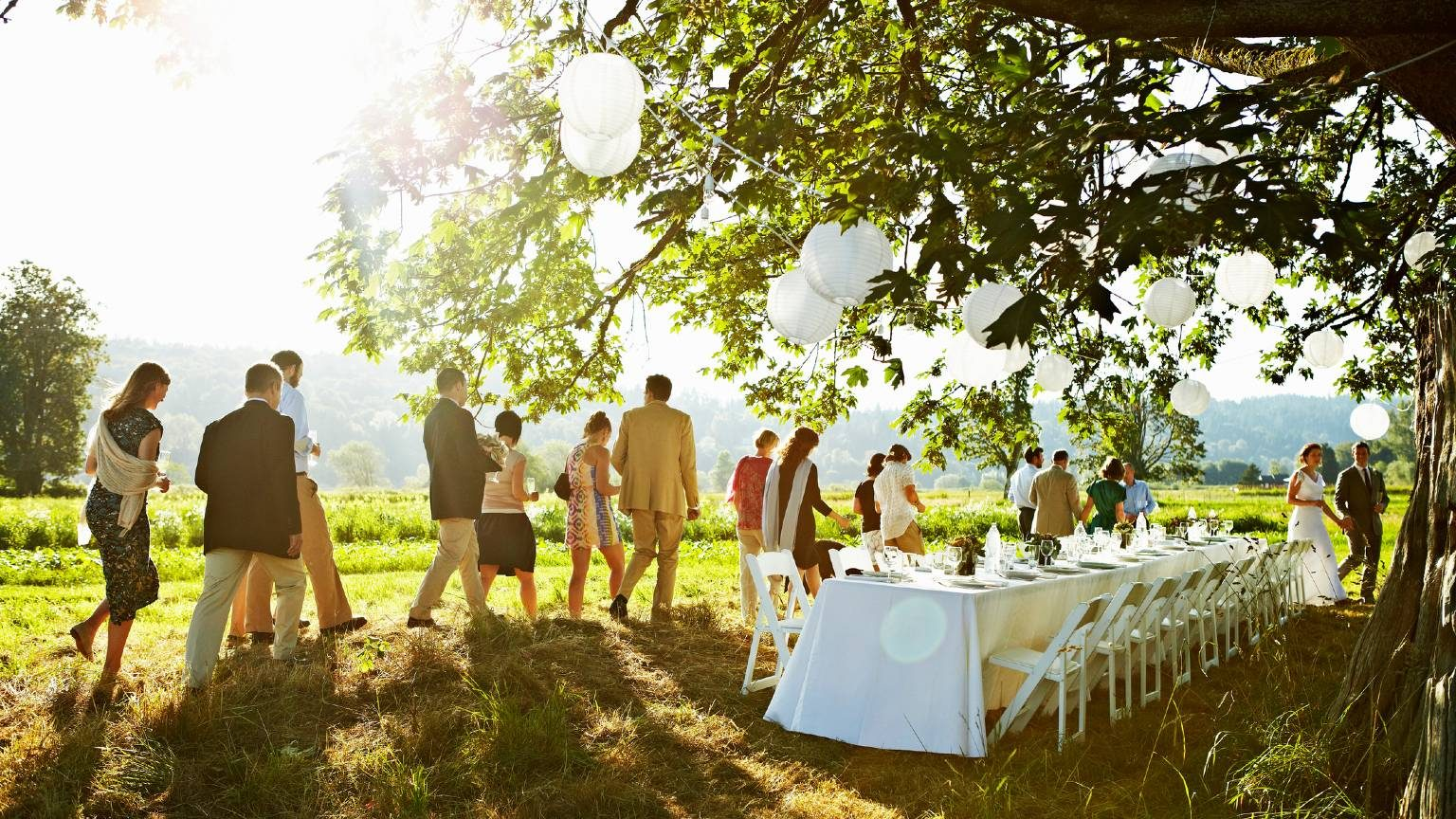 Bride and groom and wedding party walking to banquet table set for dinner outside under tree in field