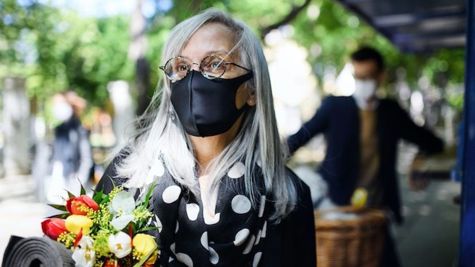Woman with white hair wearing a black face mask and carrying flowers