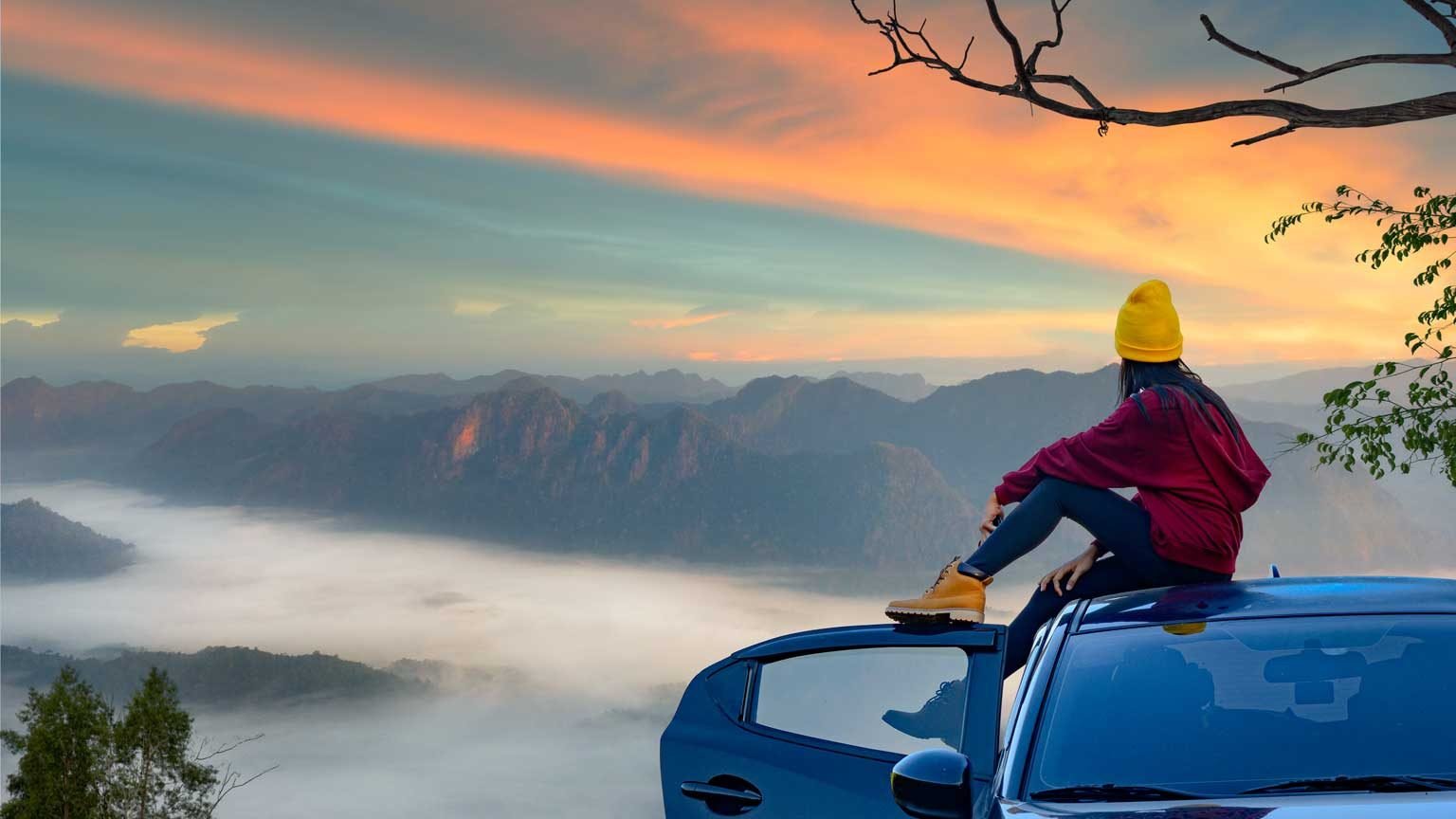 woman sitting on the car roof with enjoy the nature of mist in the mountain at sunrise morning
