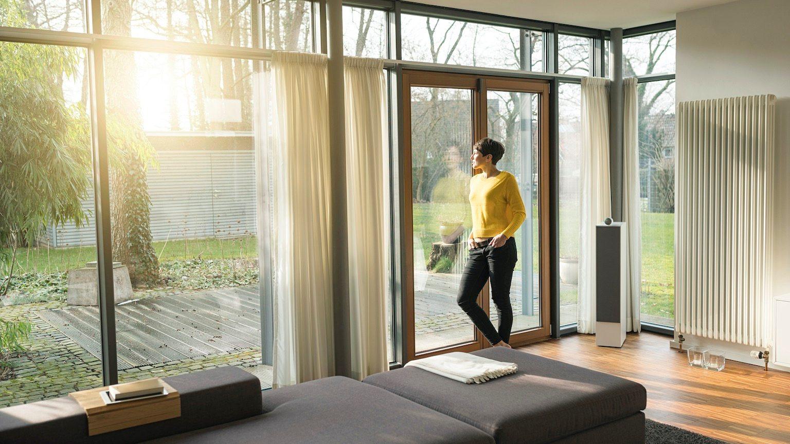 Woman standing in living room in the evening looking through terrace door