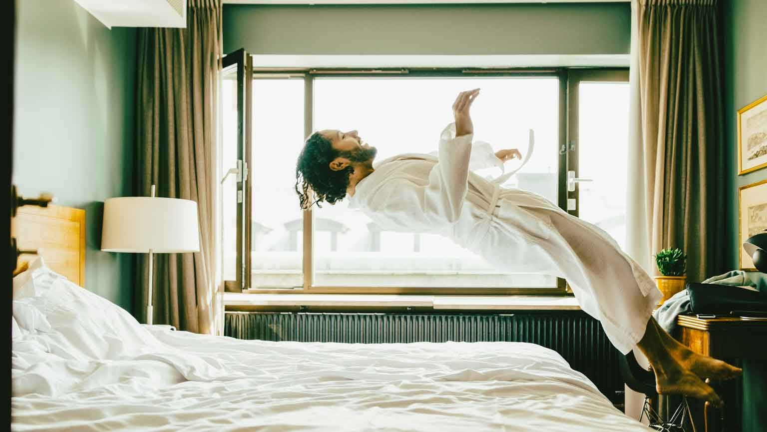Playful man wearing robe jumping on bed at hotel