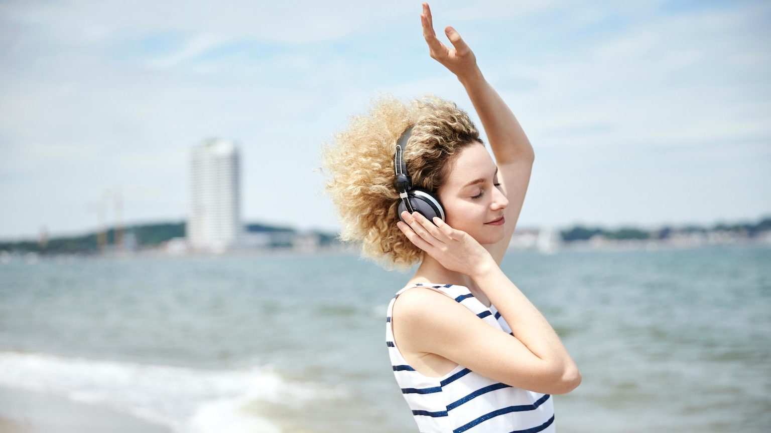 woman in front of the sea, wearing hedphones and, dancing and listening with closed eyes