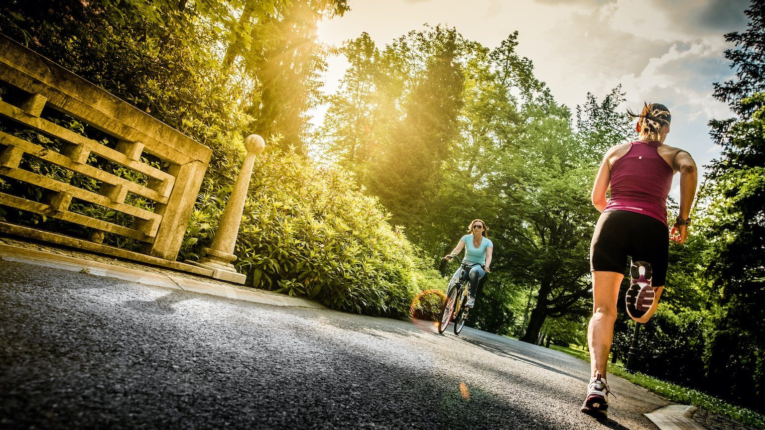 Photo of a female jogger in the park, with sun flare in the background.