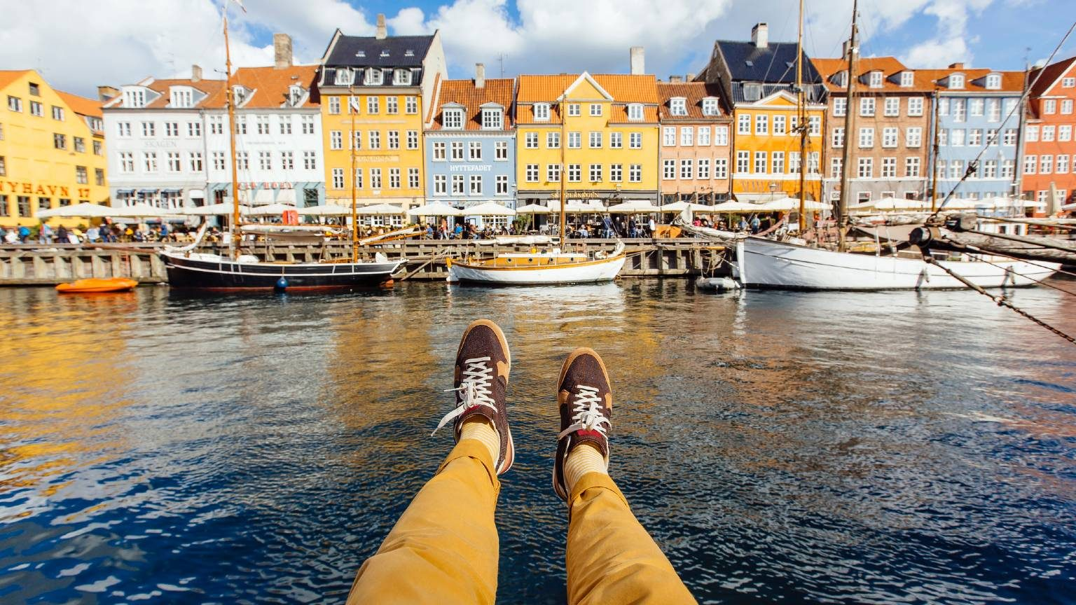 Personal perspective point of view of man sitting at the Nyhavn canal in Copenhagen, Denmark