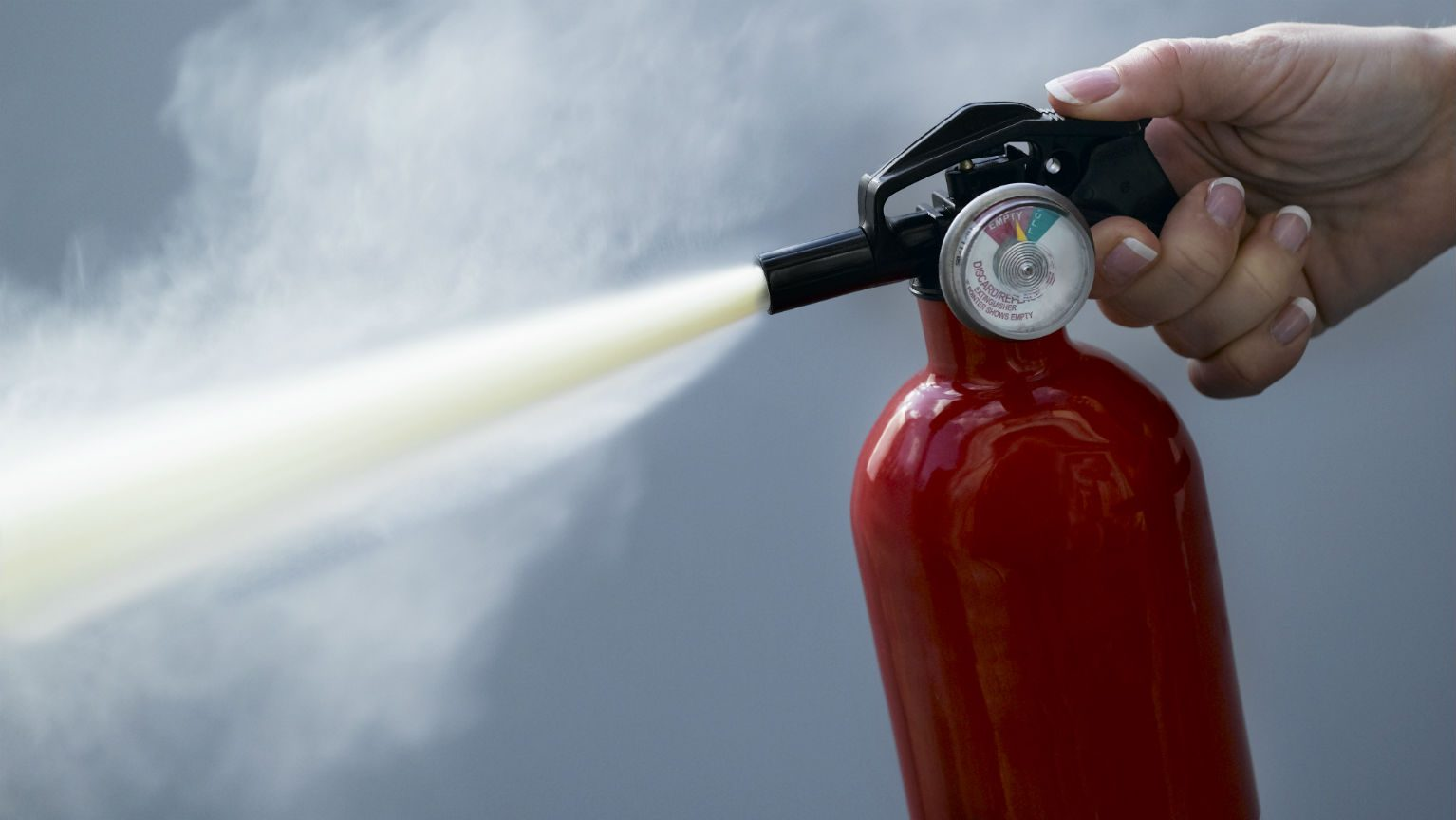 Woman spraying fire extinguisher