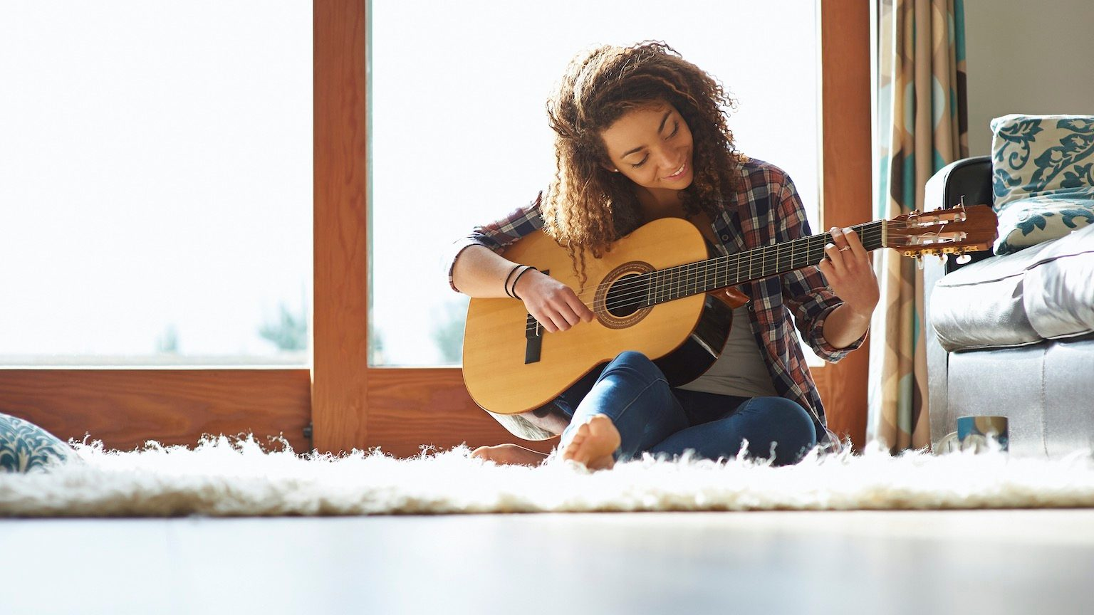 A woman sits at home and plays a guitar.