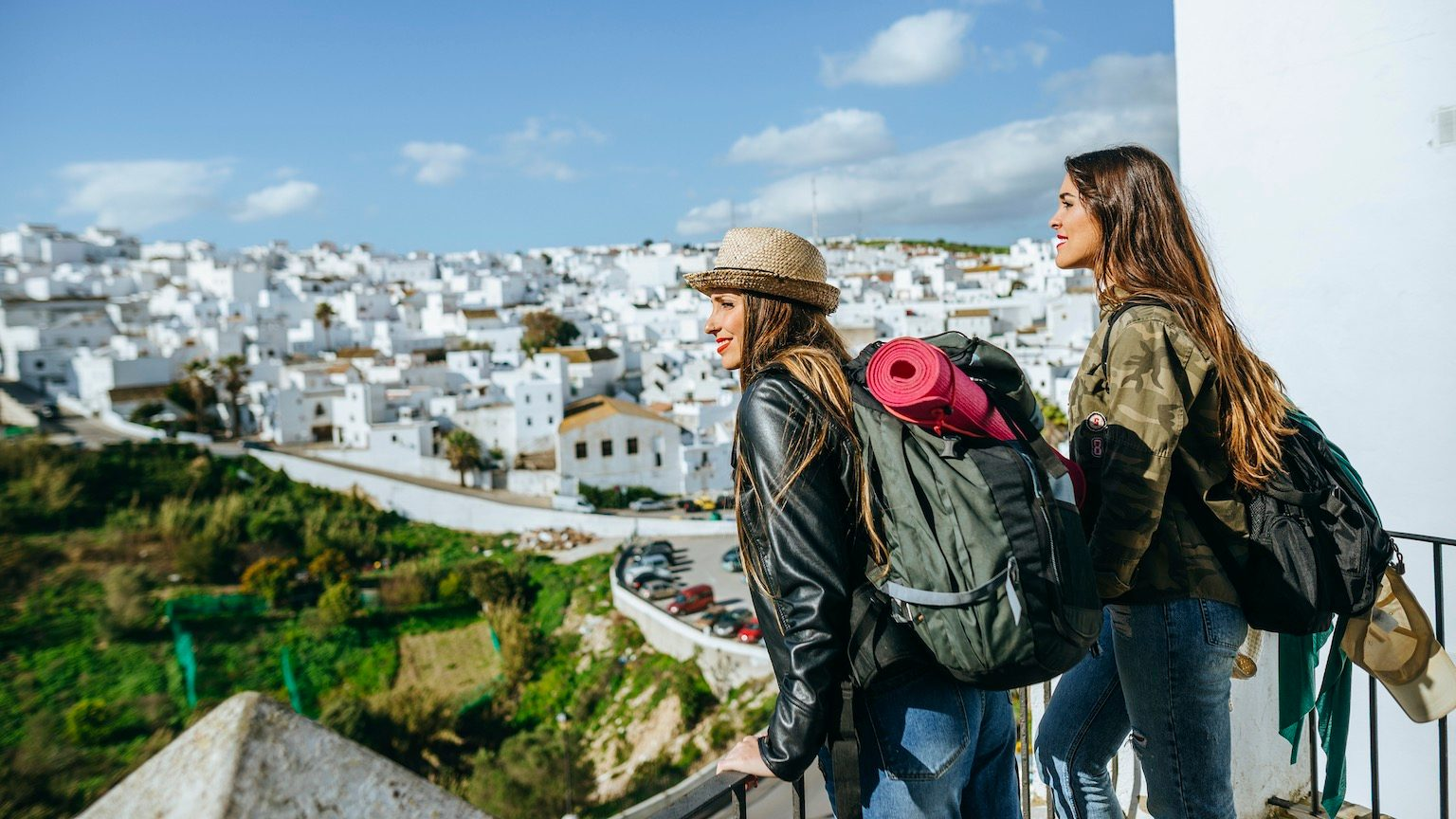 Young women looking at the landscape of Vejer de la Frontera, from the route of the white villages in Andalusia.