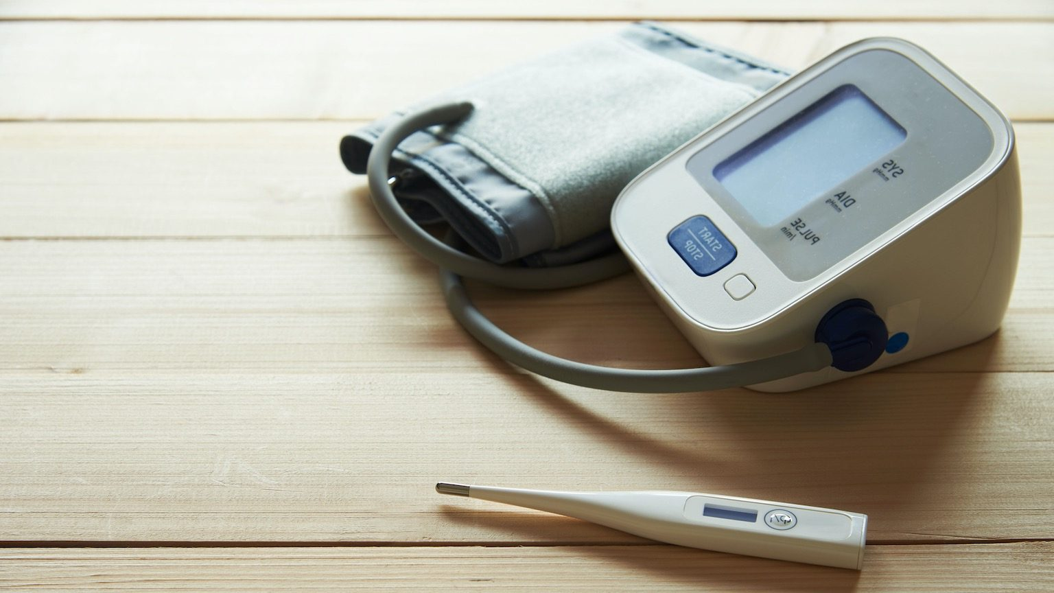 A white digital thermometer and digital sphygmomanometer on wooden background