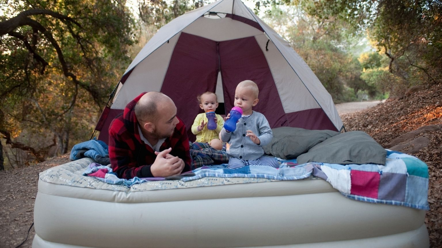 Toddler twins on camping mattress with father