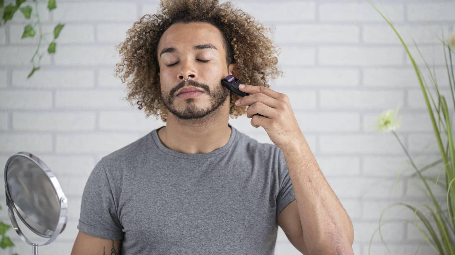 Man using a derma roller in the mirror