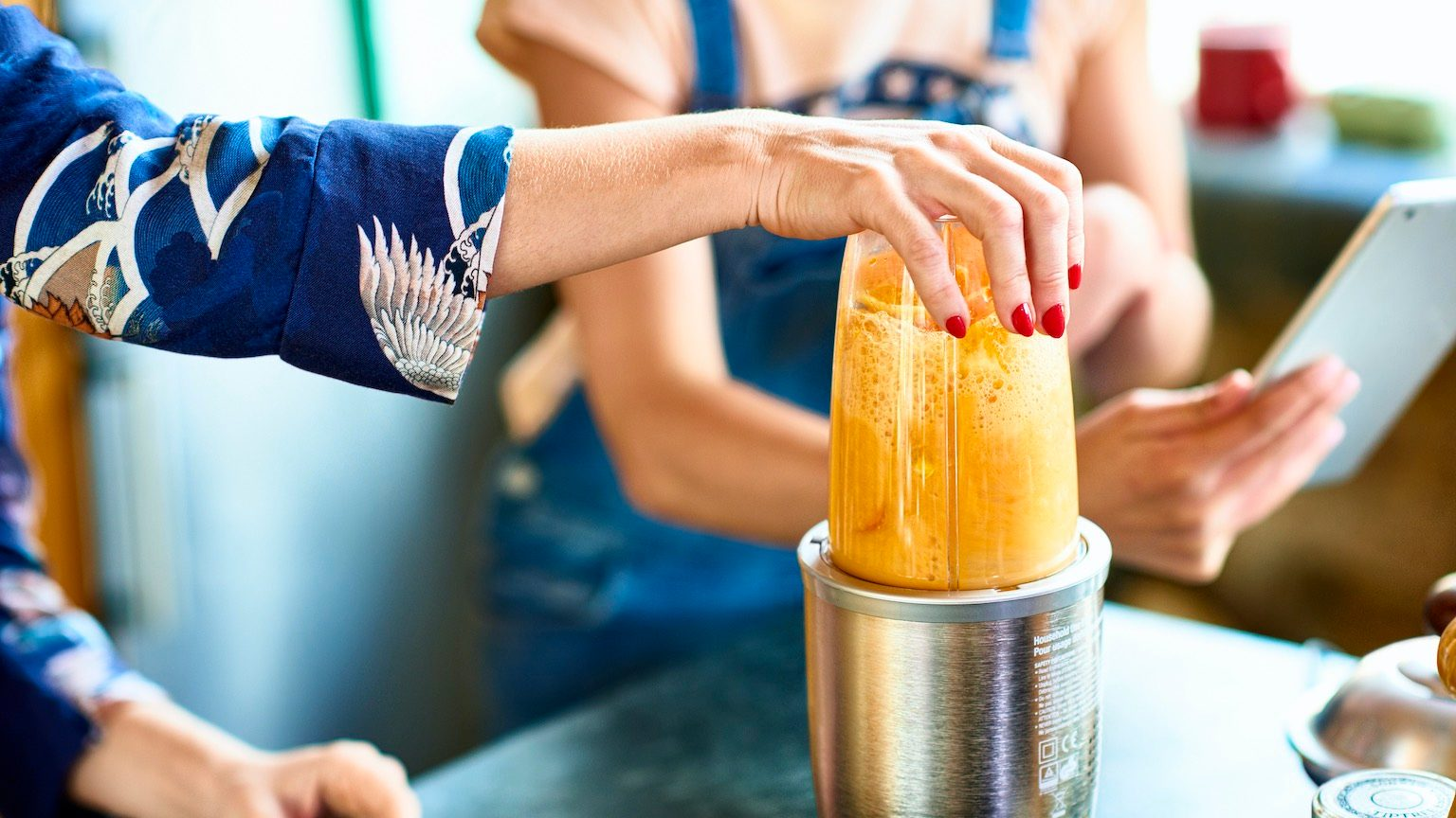 Hand of woman preparing smoothie in blender, daughter holding tablet in background