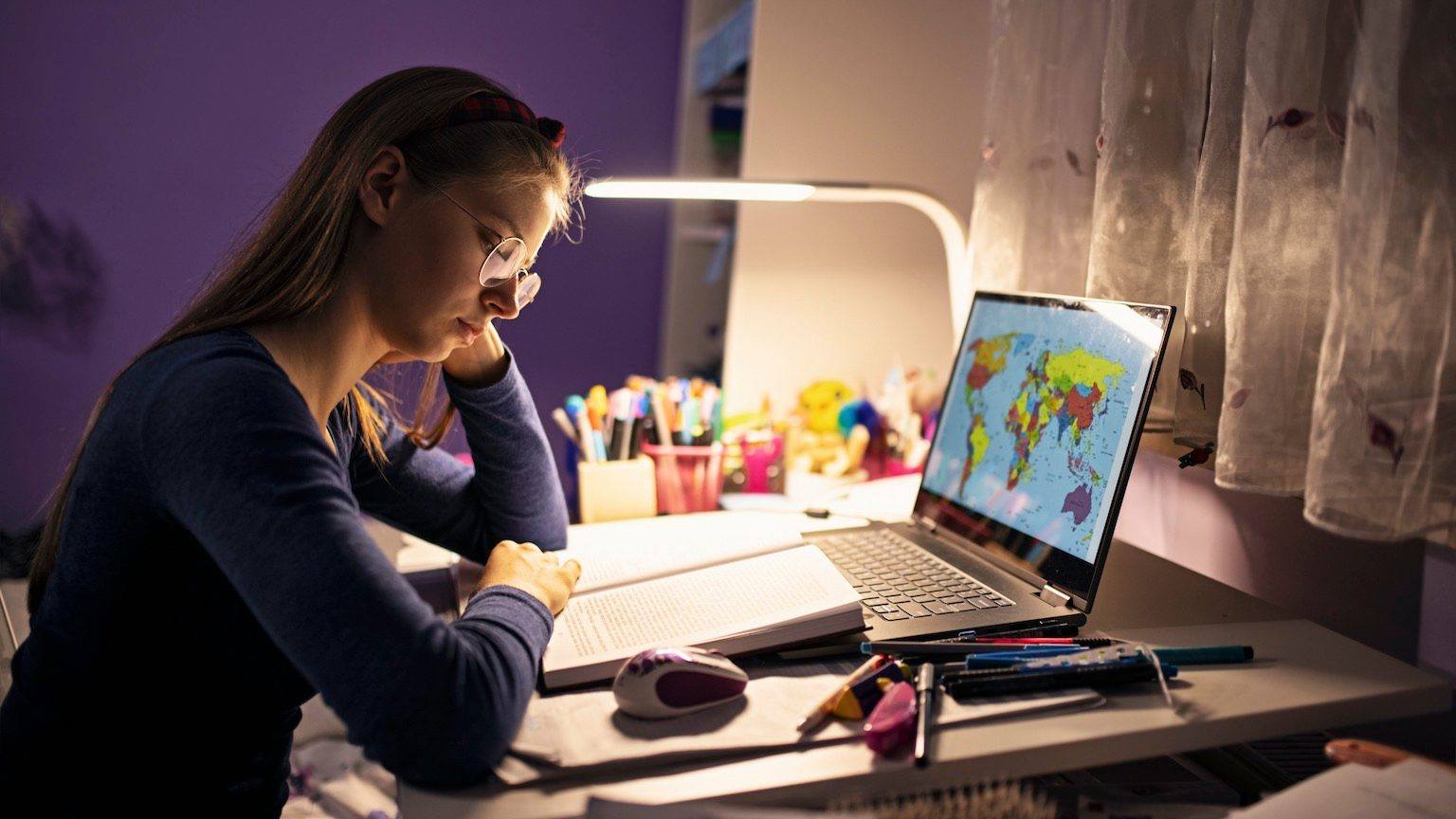 Teenage girl studying at her desk in her room. She is using task lighting to save the energy.