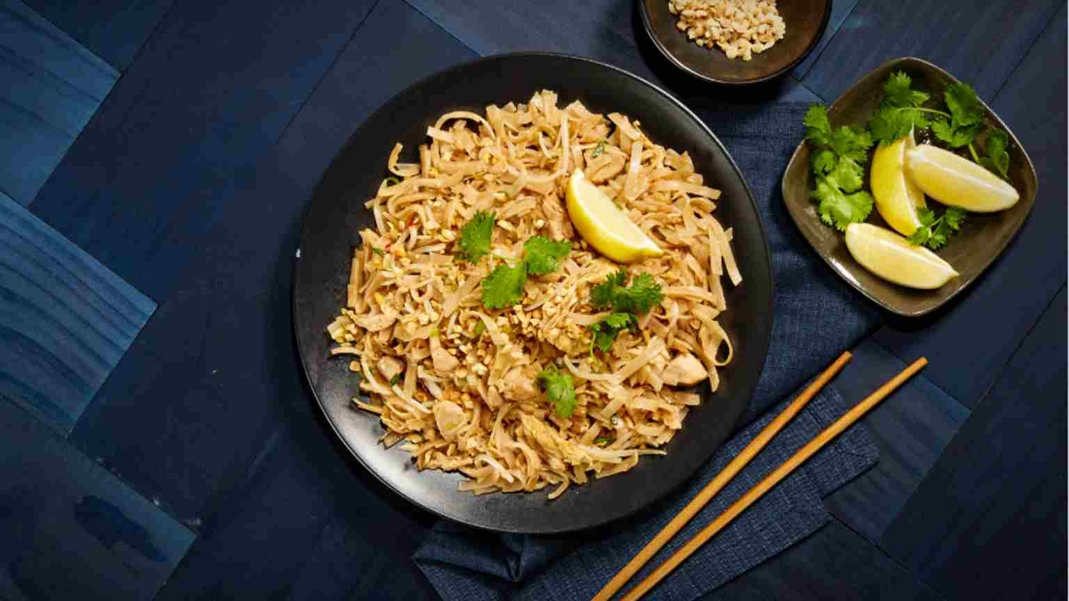 A plate of noodles with chopsticks on a table.