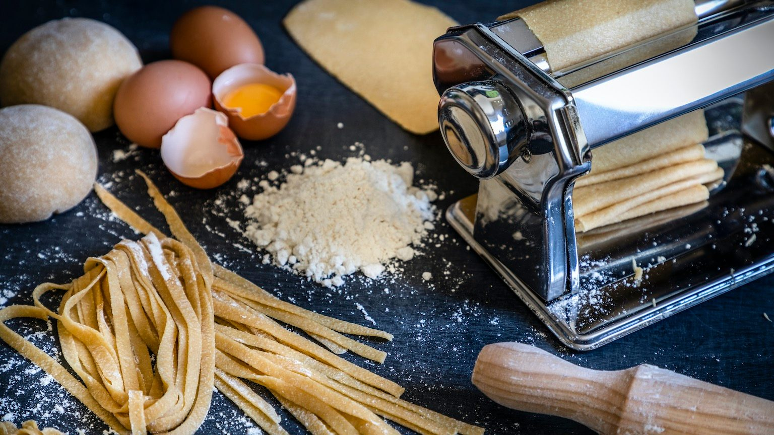 Front view of a homemade pasta machine surrounded by the ingredients for making pasta like eggs and flour. Low key DSLR photo taken with Canon EOS 6D Mark II and Canon EF 24-105 mm f/4L