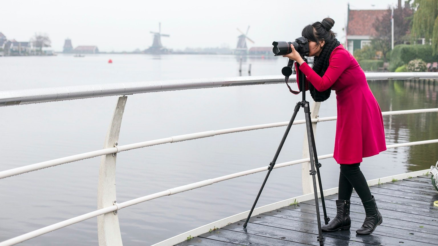 asian Girl taking picture of windmills with camera