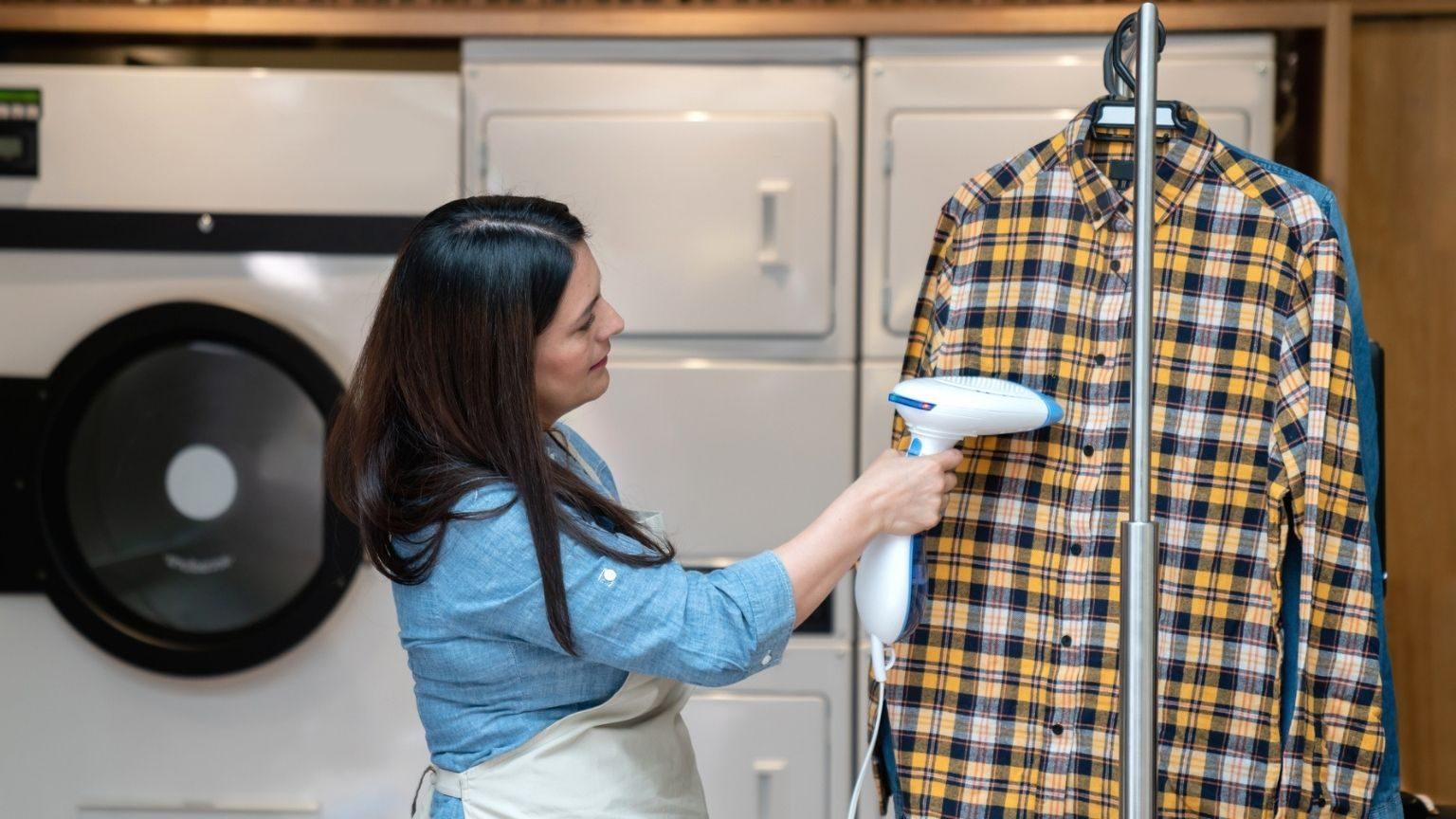Woman using a garment steamer on shirt