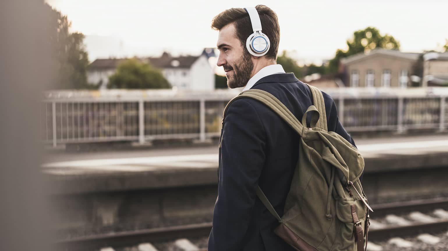 Man wearing headphones waiting for a train