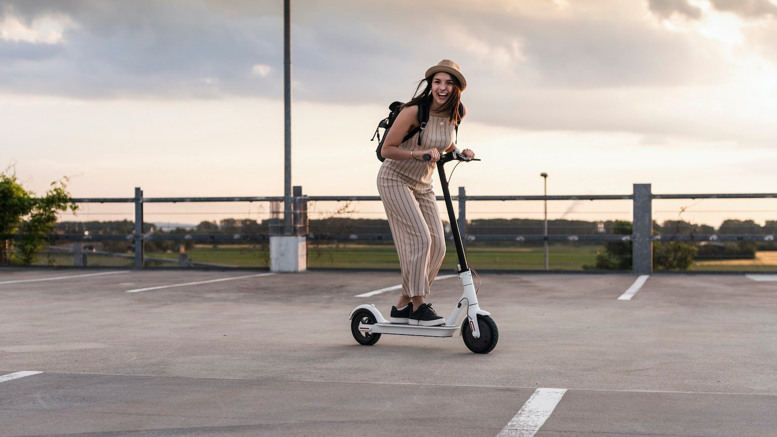 Happy young woman on electric scooter on parking deck
