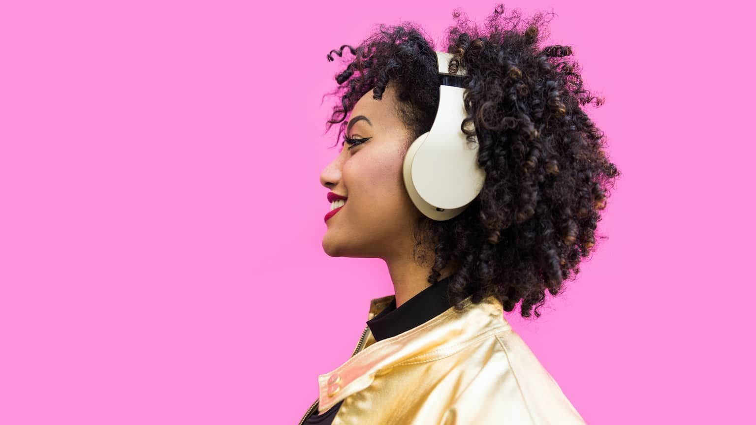 Woman wearing headphones in front of a bright pink wall