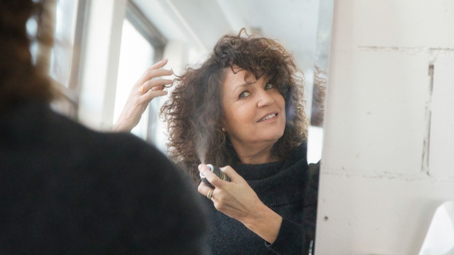 woman applying dry shampoo in front of mirror