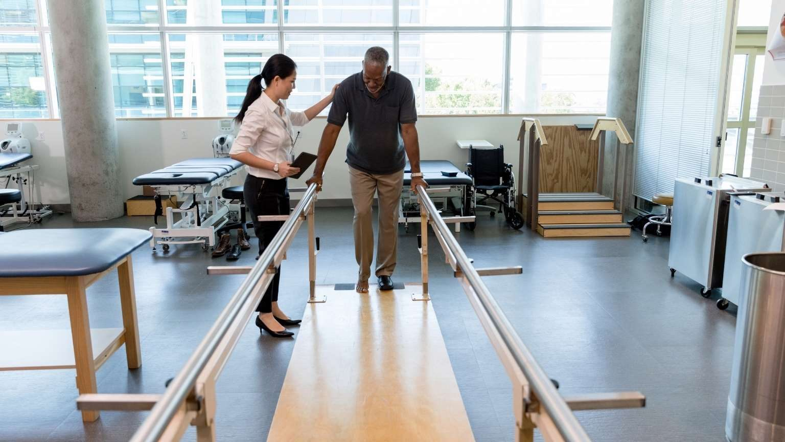 Caring female physical therapist helps stroke victim in rehab center
